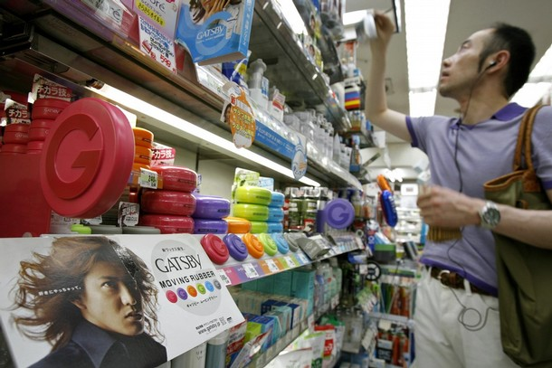 """Cosmetics maker Mandom Corp.'s Gatsby """"Moving Rubber"""" hair wax is seen on a shelf while a man picks up a cosmetic product for men at a drug store in Tokyo August 5, 2007. In a society that in many ways remains sharply defined by traditional gender roles and expectations, fashion-conscious young men are one-upping their metrosexual counterparts in the West -- it is not only acceptable for them to obsess over their hair, face and clothes, it's sexy too.. Picture taken August 5, 2007. To match feature JAPAN-COSMETICS/ REUTERS/Kiyoshi Ota (JAPAN)"""
